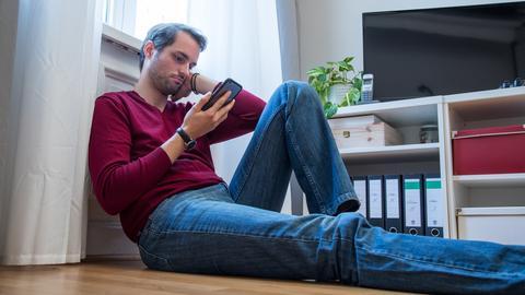 Ein Mann sitzt in einem Wohnzimmer an die Heizung gelehnt und schaut traurig auf sein Smartphone.