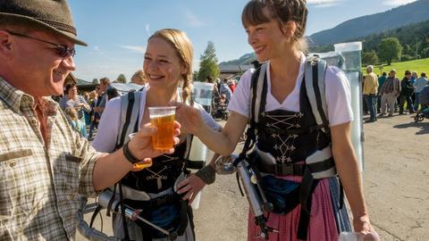 Heimkehrerin Lisa (Theresa Scholze, Mitte) und ihre Schwester Marie (Catherine Bode, re.) verkaufen Bier auf dem Volksfest.