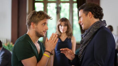 Balthasar (Stephan Luca, re.) möchte seinem Bruder Hubertus (Steve Windolf) seine neue Freundin Anastasia (Natalia Avelon) vorstellen – nicht ahnend, dass die beiden sich bereits gut kennen.