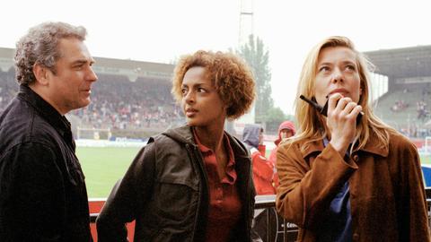 Der Trainer von Germania Bieber (Hansa Czypionka) mit den beiden Kommissarinnen Simone Dreyer (Barbara Rudnik, re.) und Carol Reeding (Dennenesch Zoudé) im Stadion.