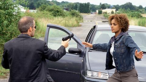 Esch (Harald Koch) versucht mit Waffengewalt, Beweismaterial von Carol Reeding (Dennenesch Zoudé) zu erpressen.