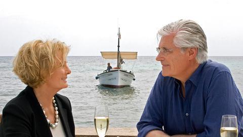 Paar trinkt Sekt vor Meereskulisse