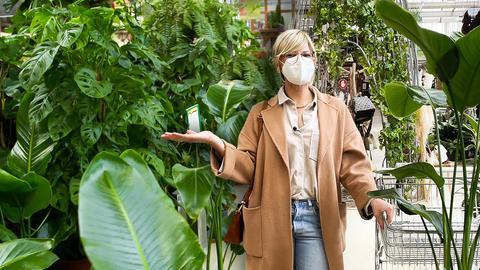Eine Frau mit FFP-2 Maske steht inmitten zahlreicher Zimmerpflanzen