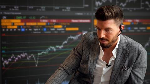 Ein Banker, im Hintergrund Bildschirme mit Börseninformationen