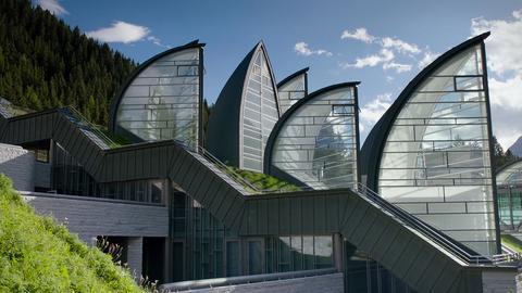 Bild eines architektonisch besonderen Gebäudes hoch in den Bergen. Es sieht aus wie eine Ansammlung gläserner Segel.