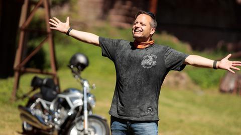 Friso Richter im Sonnenschein, im Hintergrund sein Motorrad.