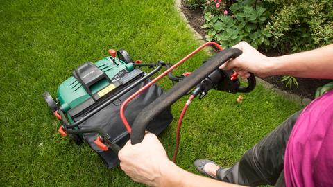 Eine Frau benutzt in einem Garten einen elektronischen Vertikutierer.