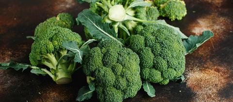 Vier frische Köpfe Brokkoli auf dunkelbraunem Untergrund.