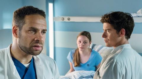 Dr. Matteo Moreau (Mike Adler, l.) ist mit Bens (Philipp Danne, r.) Verhalten vor der Patientin Sarah Hahn (Mathilde Bundschuh, M.) nicht einverstanden.