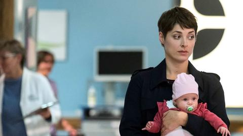 """Der Arbeitstag beginnt für Theresa Koshka (Katharina Nesytowa mit Komparsen) etwas ungewöhnlich. Sie soll spontan auf Ben Ahlbecks Tochter """"Raya"""" aufpassen."""