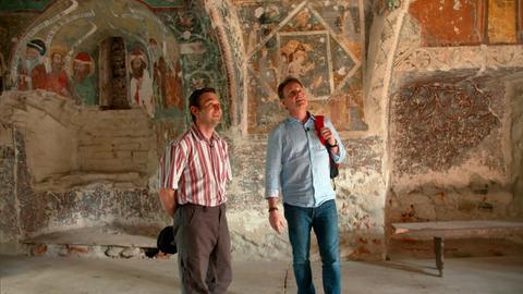 Stefan Pinnow (l) und Dan Ilica-Popescu, Kirchenführer der Kirchenburg Honigberg (rum.Harman), in der Kapelle des östlichen Turms der Kirchenburg, mit Wandmalereien aus dem 15. Jahrhundert.