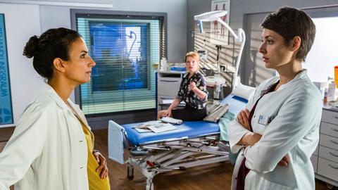 Dr. Theresa Koshka (Katharina Nesytowa, r.) und ihre Prüferin Anja Lokosch (Aline Hochscheid, M. hinten) haben keinen besonders glücklichen Start. Theresa versucht zu retten, was noch zu retten ist - mehr oder weniger erfolgreich. Dabei ist sie ahnungslos, dass sie auch noch Dr. Leyla Sherbaz (Sanam Afrashteh, l.) Freundin, gegenüber steht.