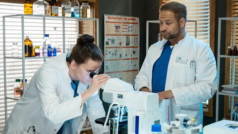 Tom Zondek (Tilman Pörzgen, l.) und Dr. Matteo Moreau (Mike Adler, r.) suchen im Labor nach Spuren einer möglichen Vergiftung.