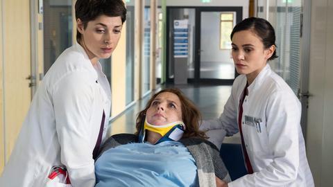 Die Patientin Tina Tönnissen (Nicole Johannhanwahr, M.) bereitet den beiden Ärztinnen Theresa Koshka (Katharina Nesytowa, l.) und Rebecca Krieger (Milena Straube, r.) Sorge. Sie verliert das Gefühl in ihren Beinen.