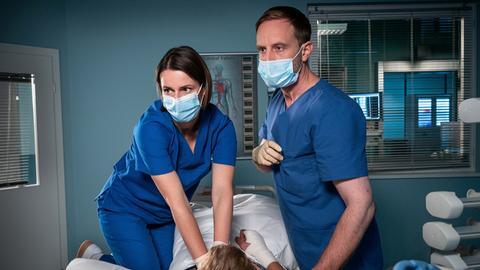 Mick Mohnhaupt (Joseph Bundschuh, mi.) hat plötzlich einen Herzstillstand. Dr. Maria Weber (Annett Renneberg, li.) und Dr. Kai Hoffmann (Julian Weigend, re.) versuchen ihn zurückzuholen..