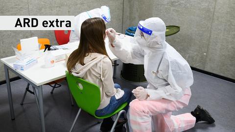 ARD extra vom 16.02.2021: Eine Person sitzt auf einem Stuhl und bekommt einen Corona-Abstrich,