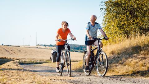 Zwei Personen auf Fahrrädern in der Natur.