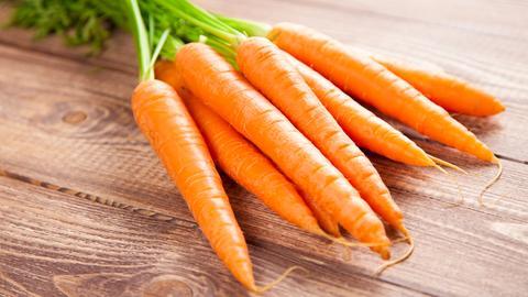 Ein Bund Karotten liegt auf Holzgrund.