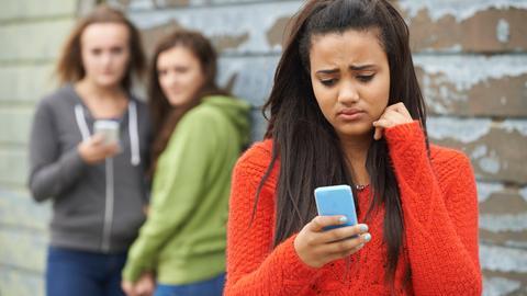 Ein junges Mädchen schaut unglücklich auf ihr Handy. Im Hintergrund stehen zwei Mädchen mit einem Handy und schauen auf das Mädchen im Vordergrund.