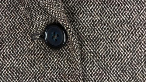 Detailaufnahme einer Tweed-Jacke mit schwarzem Knopf.