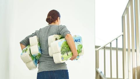 Eine Frau voll bepackt mit Klopapier steigt eine Treppe hoch.