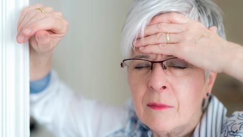 Eine Seniorin mit kurzen weißen Haaren hält sich mit schmerzverzerrtem Gesicht und geschlossenen Augen die Hand an die Stirn.