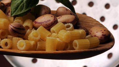Rohe Nudeln und Bohnen auf einer Schöpfkelle.