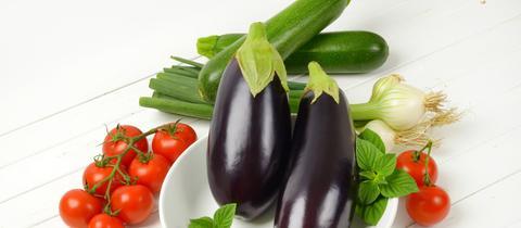 Frische Zucchini, Auberginen, Cocktailtomaten und Frühlingszwiebeln liegen teils in einem Teller, teils auf hellem Grund.