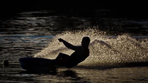 Ein einzelner Wakeboarder bei Sonnenuntergang in Aktion. Es herrscht goldene Lichtstimmung und das Wasser spritzt.