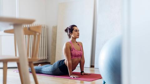 Eine Frau macht Pilates auf einer Matte in ihrem Wohnzimmer.