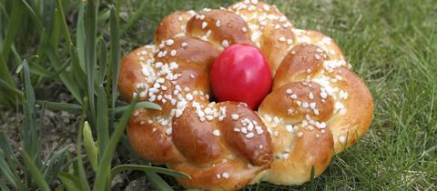 Ein gebackener Osterkranz mit einem roten Osterei in der Mitte liegt im Gras neben drei eingepflanzten Osterglocken.