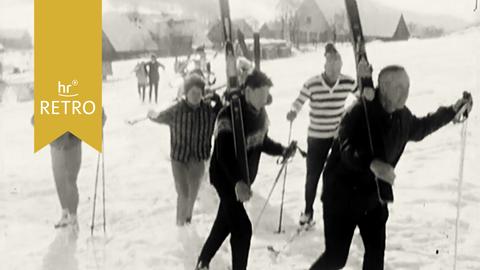 ARD Retro Skikurs Rhön: Die Ski-Schüler*innen mit geschulterten Ski-Brettern auf dem Weg zum Berg.