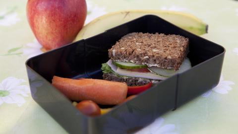 Eine Brotbüchse, gefüllt mit Vollkornbrot, Gemüse und Obst.