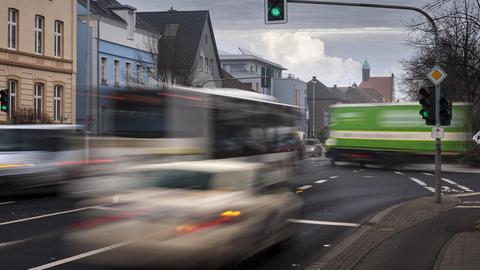 Taxi, LKW und Bus im fließenden Verkehr an einer Kreuzung (aufgenommen mit Langzeitbelichtung).
