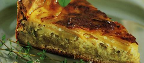 Ein Stück Zwiebelwähe mit Käseguss auf einem Teller.