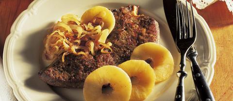 Kalbsleber Berliner Art auf einem Teller angerichtet mit Apfelscheiben und Zwiebeln.