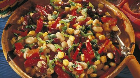 Eine große Tonschüssel voll mexikanischer Salat mit Bohnen, Paprika, Chili und Maiskörnern.