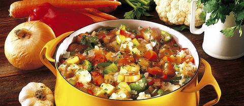 Gemüseeintopf in einem großen gelben Topf auf Holzunterlage. Knoblauch, Zwiebeln, Paprika, Karotten, Tomaten, Fenchel, Blumenkol und Petersilie sind im Hitnergrund zu sehen.