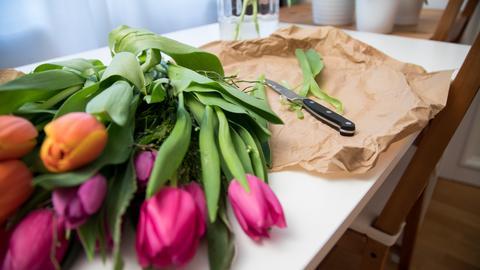 Ein Strauß bunter Tulpen liegt neben einem Schnittmesse auf braunem Einwickelpapier. Im Hintergrund steht eine Vase aus Glas.