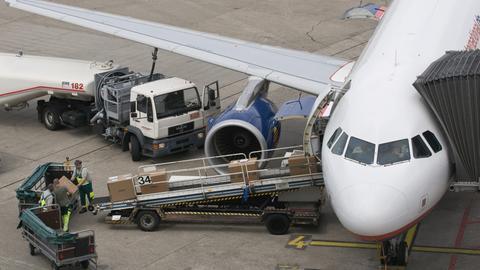 Ein Flugzeug wird auf dem Vorfeld betankt und beladen.