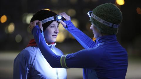 Eine Joggerin mit Stirnlampe zieht einer anderen Joggerin das Band ihrer Stirnlampe zurecht.