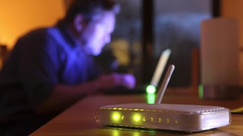 Funktionierender Router, verteilt eine eingehende DSL-Verbindung über W-Lan, drahtlos per Funk, an Computer. Im Hintergrund ist unscharf ein Computernutzer in einer Wohnung zu sehen.