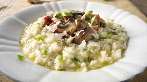 Klassisches Risotto mit wilden Steinpilzen und Speck auf einem weißen Teller angerichtet.