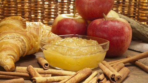 Glasschale mit frischer Apfelmarmelade und Zimtstangen.