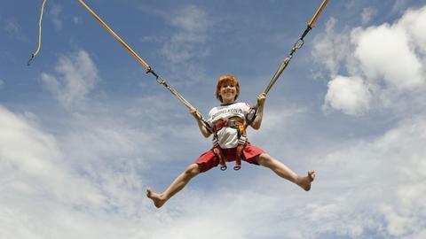Ein Junge hüpft an einem Bungee-Trampolin und fliegt in die Luft.