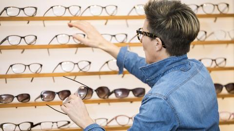 Eine Frau mit Brille sucht sich beim Optiker vor einem Brillen-Regal mehrere Brillen aus.
