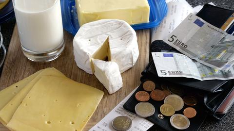 Milchprodukte, wie Butter und Käse, neben einer geöffneten Brieftasche.