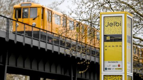 Eine U-Bahn fährt an dem Hinweisschild des Mobilitätshub Jelbi vorbei. Eine Auswahl von verschiedenen Sharing-Fahrzeugen unterschiedlicher Anbieter, vom Auto, über Fahrräder und Roller, stehen seit dem 12. April 2019 zur Nutzung bereit.