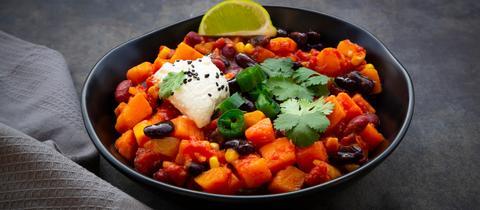 Eine Schüssel mit Chili sin Carne, garniert mit Koriander und einer Limettenspalte.