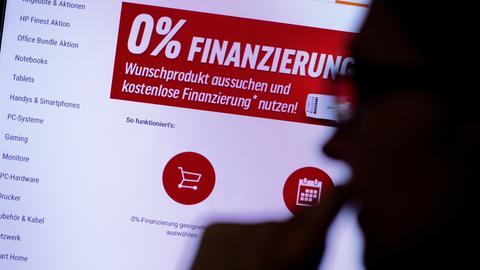 Eine Frau schaut sich auf einer Website für Technik-Produkte die Werbung für eine Null-Prozent-Finanzierung an.